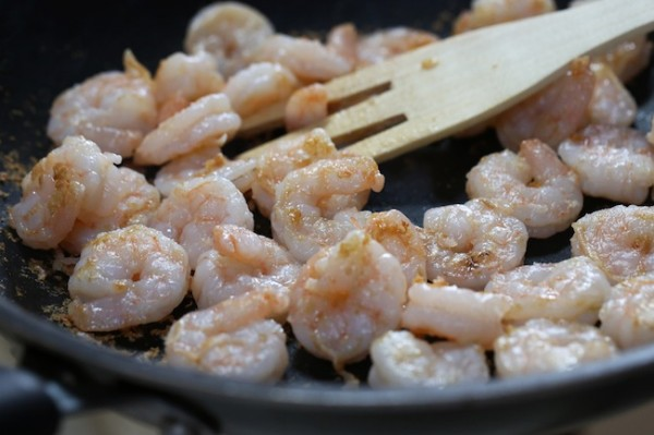 Coat the shrimp with cornstarch. Heat a large skillet or wok on high heat; add oil and cook.